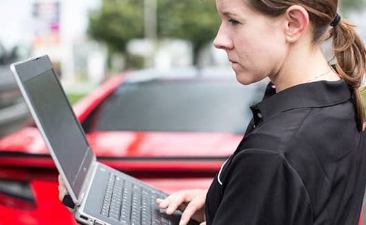 Woman with laptop in front of Curva Red NSX.