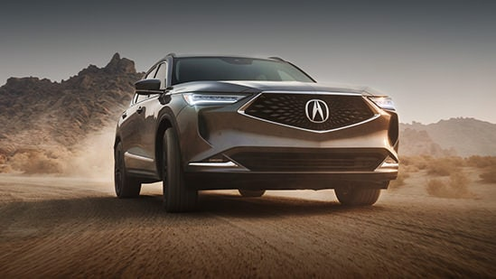 2022 Acura MDX Advance in Liquid Carbon Metallic driving with a desert landscape