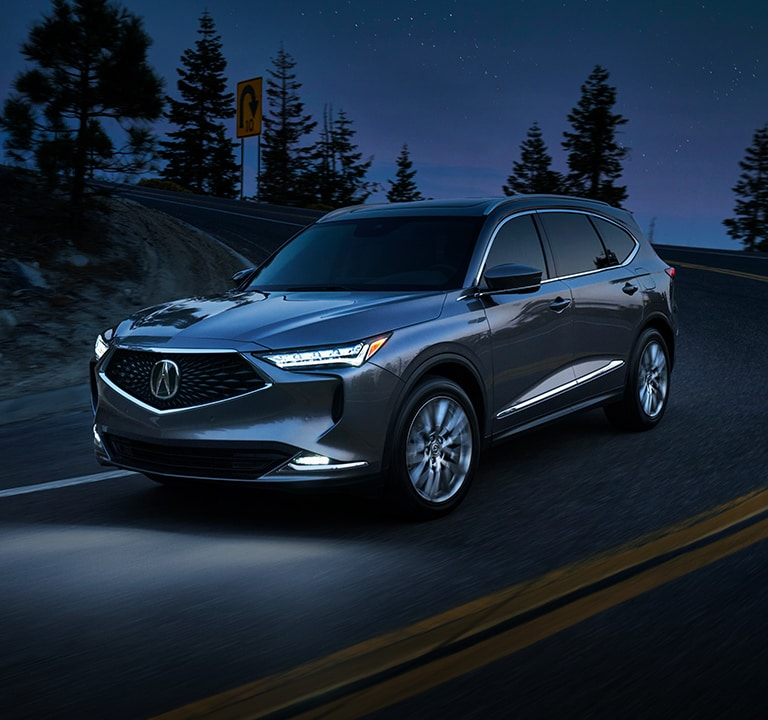 2022 Acura MDX Advance in Liquid Carbon Metallic driving at night