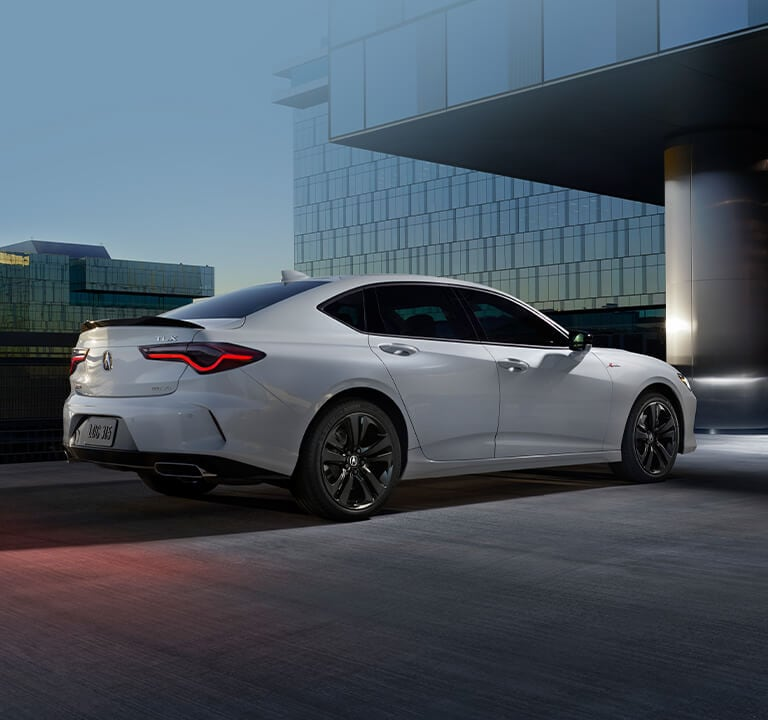Acura TLX 2021 A-Spec® drivint at night in a cityscape